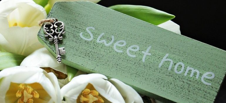 sweet home inscription in a green piece of wood and a key