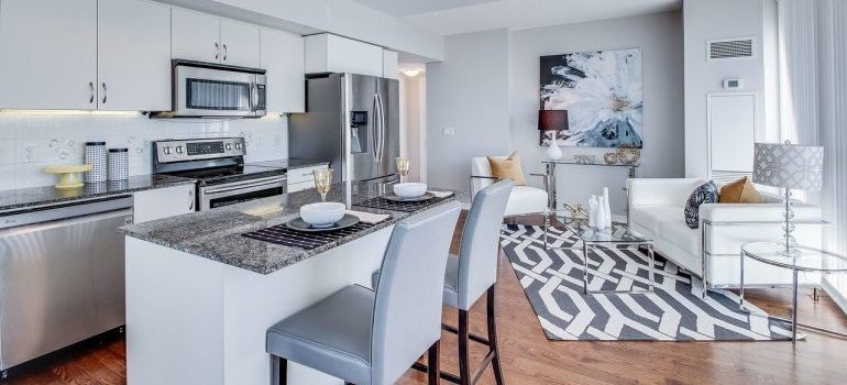 A kitchen and a living room in a condo.