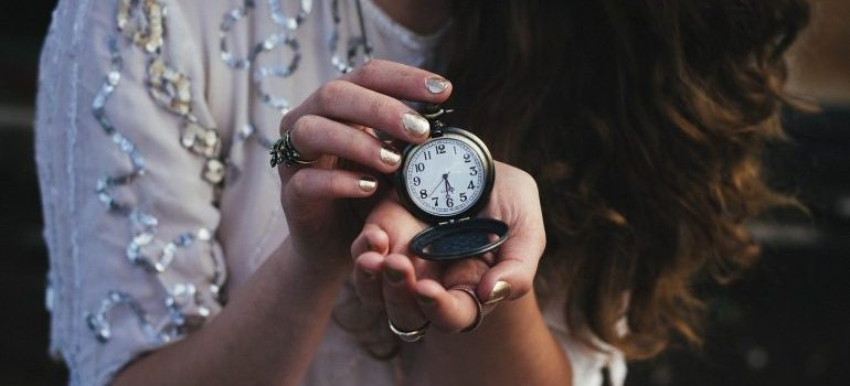 A woman holding a pocket watch.