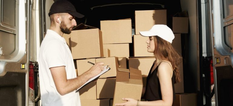 Man and woman in front of moving truck