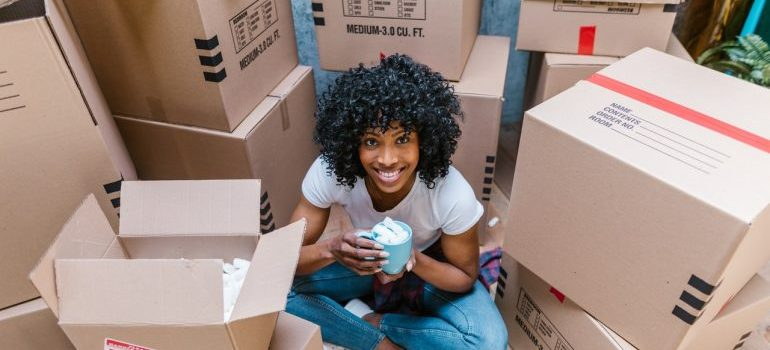 woman sitting in a pile of moving boxes