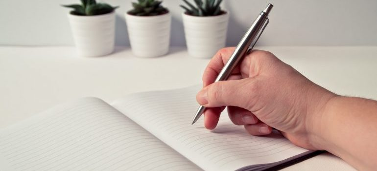 A person writing in a notebook.