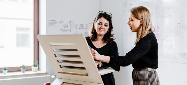 Two women discussing over a board.