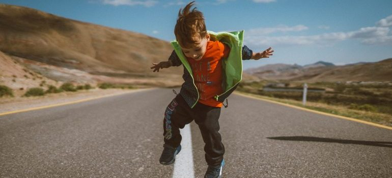 child jumping on the road