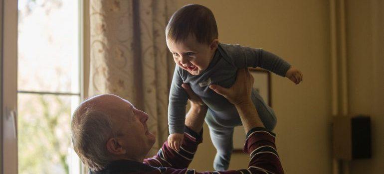 A senior holding his grandchild