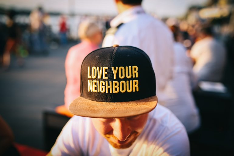 """A man with a """"Love your neighbor"""" hat."""