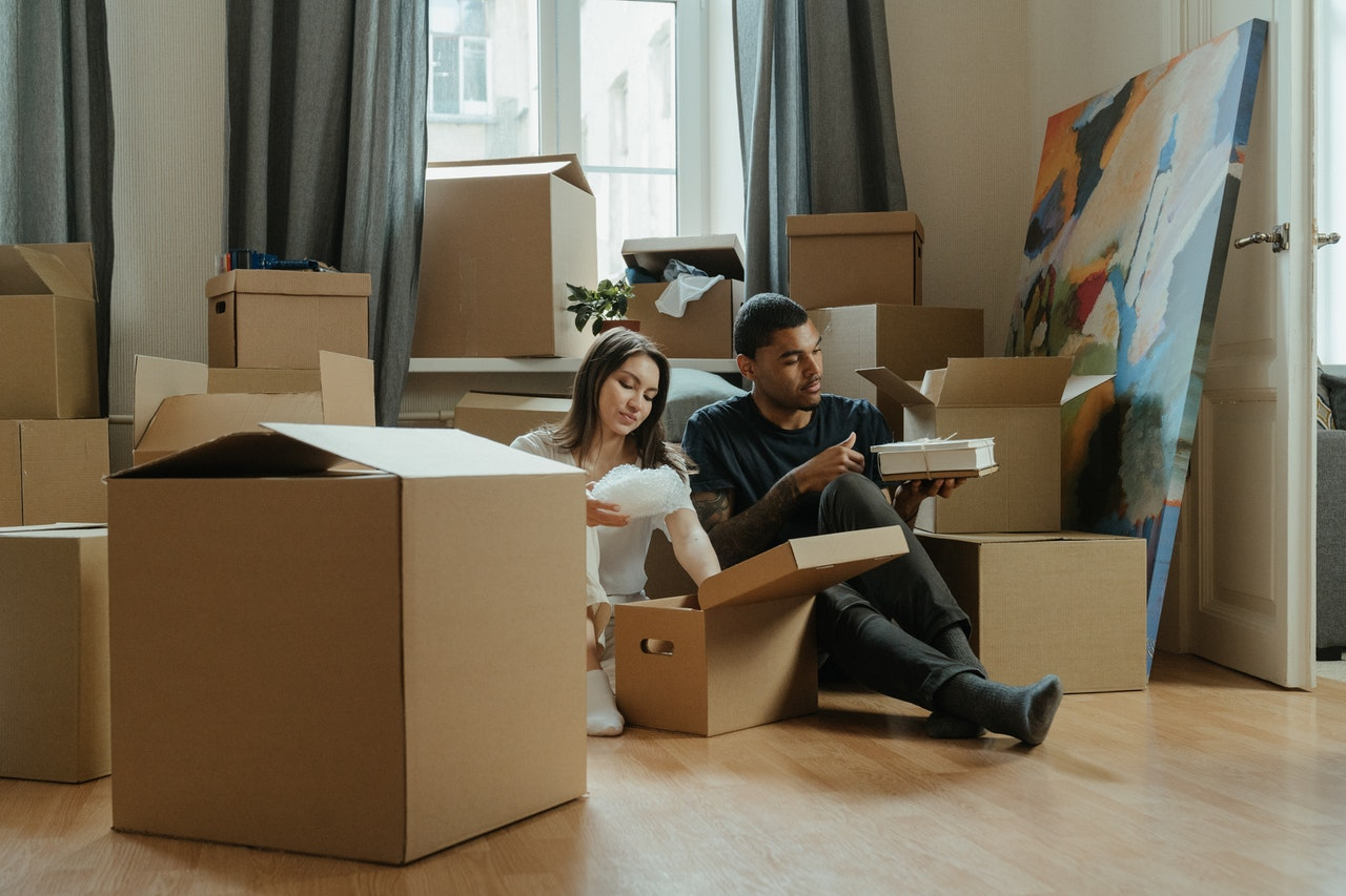 a couple sitting on the floor between a pile of cardboard boxes