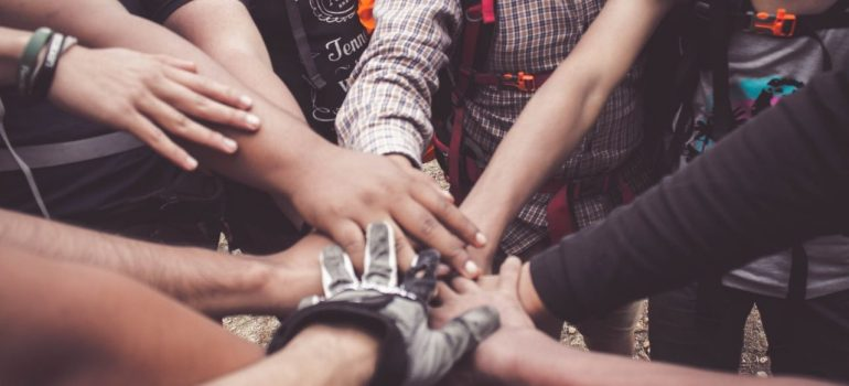 several people putting their hands together in the center