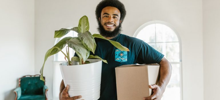 East York mover holding a box and a plant