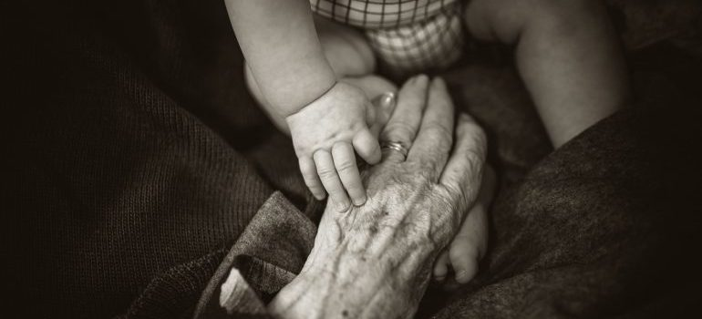 A senior women holding her grandchild's hand before the move