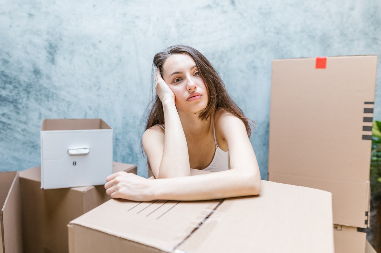 A woman thinking about how many moving boxes do you need for a successful move.