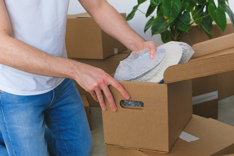 A person placing breakables in a box - pack fragile items