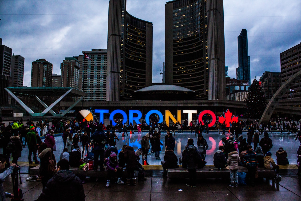 a night-time picture of downtown Toronto with buildings in the background and people near the fountain