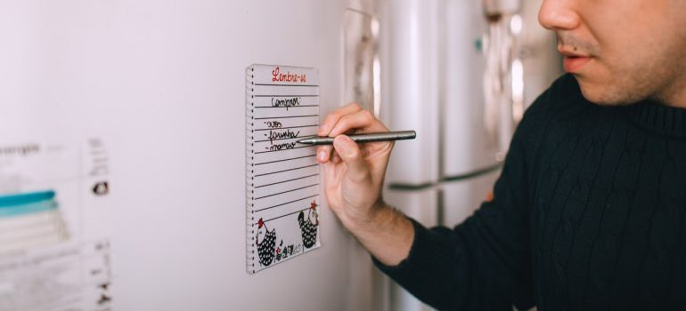 man writing down on the moving checklist on the fridge